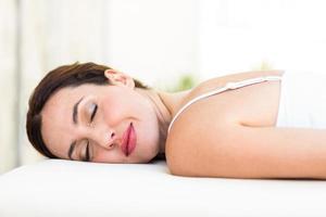 lugn kvinna som ligger på massagebordet foto