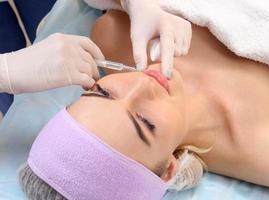vacker kvinna får en injektion i läpparna. foto
