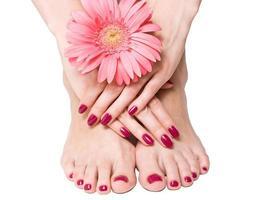 närbild av manicured och pedikyr naglar med blomma
