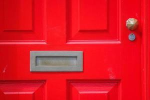röd dörr med mässingsbrevlåda foto