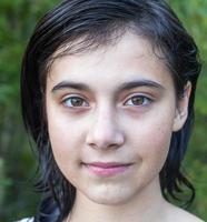 närbild porträtt av en ung mörkhårig flicka utomhus. foto