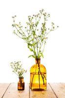 växtmedicinskoncept - flaska med kamomill på träbord foto