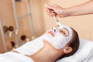 attraktiv kvinna med mask i spa salong foto