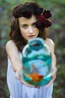 ung vacker flicka med guldfisk foto