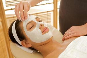 närbild av ung kvinna som får ansiktsbehandling foto