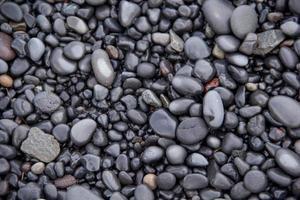 våta svarta och grå vulkaniska stenar i Island foto