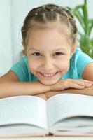 vacker liten flicka med bok foto