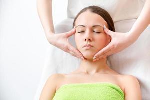 massör gör massage av ansiktet på brunetten i en handduk foto