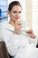 ung kvinna kopplar av med en kopp te foto