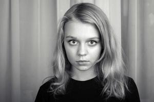 allvarlig blond kaukasisk flicka, studio porträtt foto