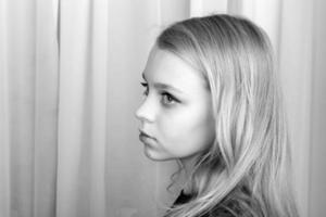 allvarlig blond kaukasisk flicka, monokrom stående