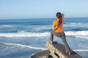 kaukasisk kvinna som utövar yoga vid kusten foto