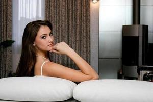 ung kaukasisk allvarlig kvinna som sitter på soffan foto