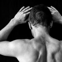 stark muskulös ung kaukasisk man står nära den svarta väggen