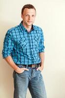 studiostående av den unga kaukasiska mannen i blå skjorta foto