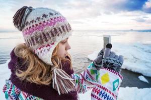 liten blond kaukasisk tjej som tar bilder på sin smartphone foto