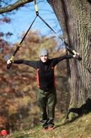utomhusupphängningsträning i skog - kaukasisk man vid träd