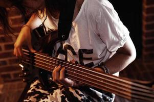 tonårs kaukasiska puk flicka sitter och spelar basgitarr närbild foto