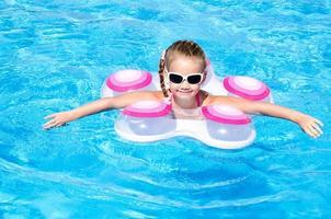 leende liten flicka i poolen foto