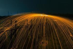 fyrverkeri duschar med heta glödande gnistor från snurrande stålull. foto