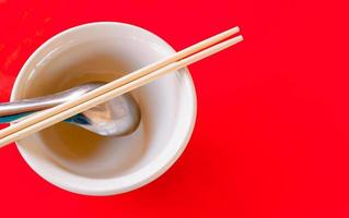 risskål och sked och pinnar på det röda bordet foto