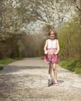 ung flicka ridning skoter på väg genom parken foto