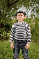 glad liten pojke i en färgglad blå hatt foto