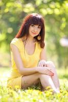 ung kvinna i parken med blommor