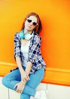 vacker flicka i solglasögon och hörlurar mot det färgglada eller foto
