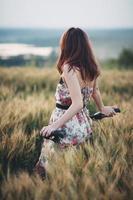 vacker ung kvinna med cykel i ett vetefält foto