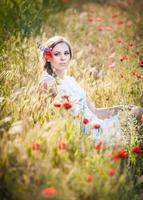 ung flicka i vit klänning på gyllene vetefält foto