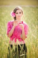 ung flicka i rosa på gyllene vetefält foto