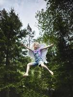 flicka som bär vingar och hoppar i skogen foto