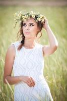 ung flicka i vit klänning med vilda blommor krans utomhus