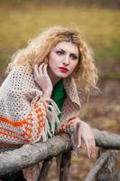 blond tjej som bär grön blus och stort sjal poserar utomhus