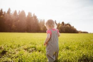 liten flicka går i parken foto