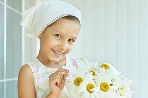 liten flicka med dasier blommor foto