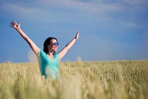 vacker flicka i ett fält mot himlen foto