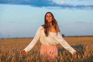 vacker brunett dam i vetefält vid solnedgången foto