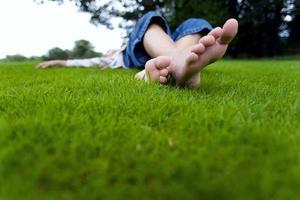 tonårsflicka som kopplar av i gräset foto