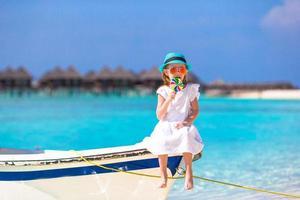 bedårande liten flicka med klubbor som sitter på båten foto