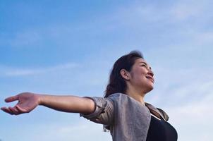 vacker kvinna med öppnade armar som uttrycker frihet foto