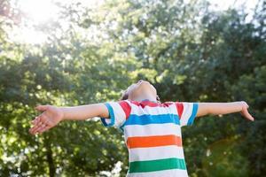 glad liten pojke i parken foto