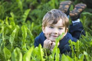liten pojke ligger i gräset i parken. foto