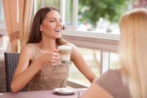 glada unga kvinnliga vänner skvallrar på café foto