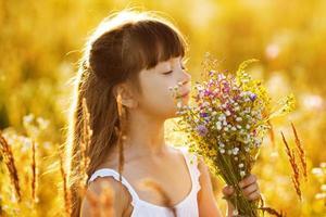 glad tjej med en bukett med vilda blommor foto