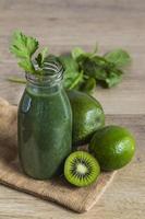 grön smoothie i en glasflaska med ingredienser foto