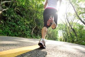 hälsosam livsstil fitness sport kvinna kör på skogsvägen foto