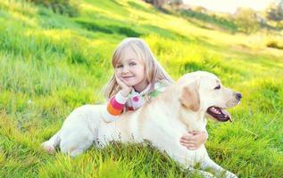 lyckligt barn och labrador retriever hund som ligger på gräset foto