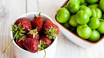jordgubbar i en kopp och körsbärsplommon på en bakgrund foto